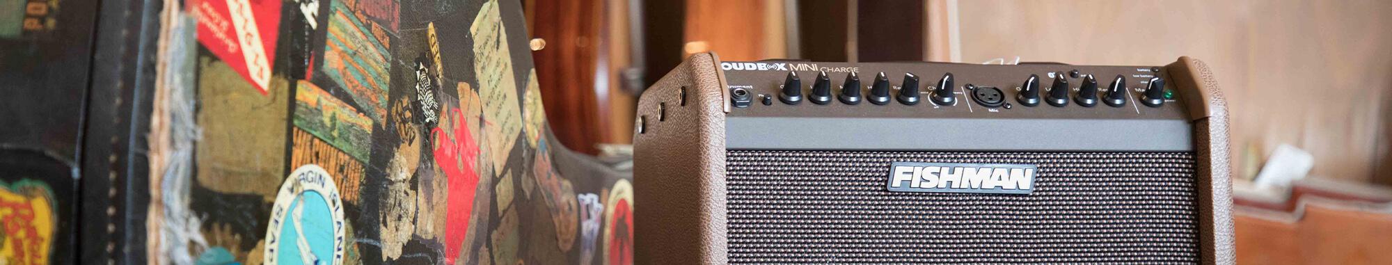 Fishman Loudbox Mini Charge acoustic amplifier next to an acoustic guitar case