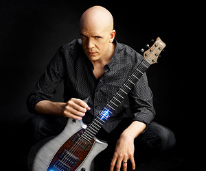 Devin Townsend posing with electric guitar with Fluence pickups
